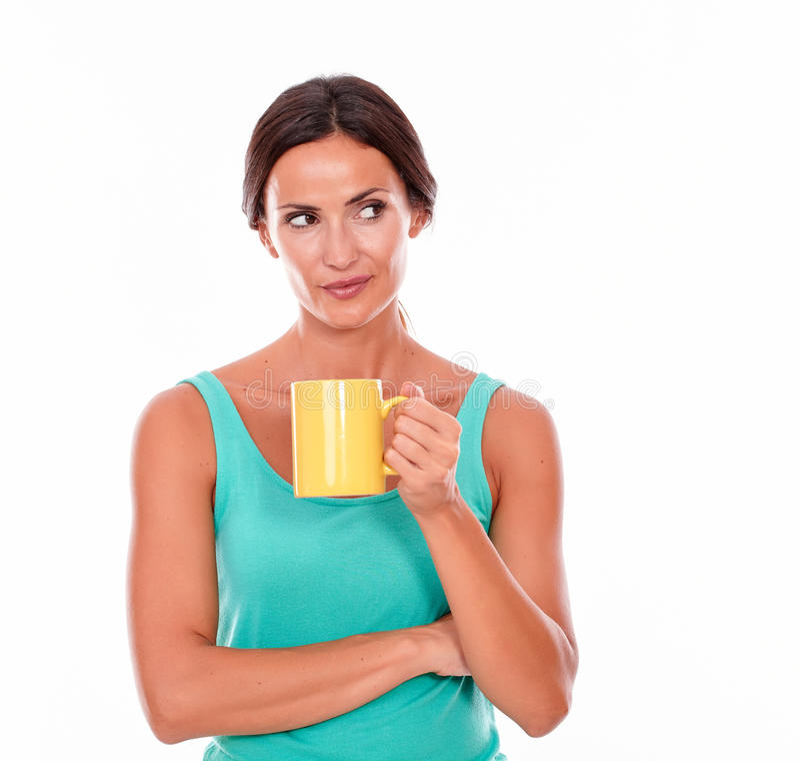 Denkende Brunettefrau mit Kaffeetasse stockfotografie