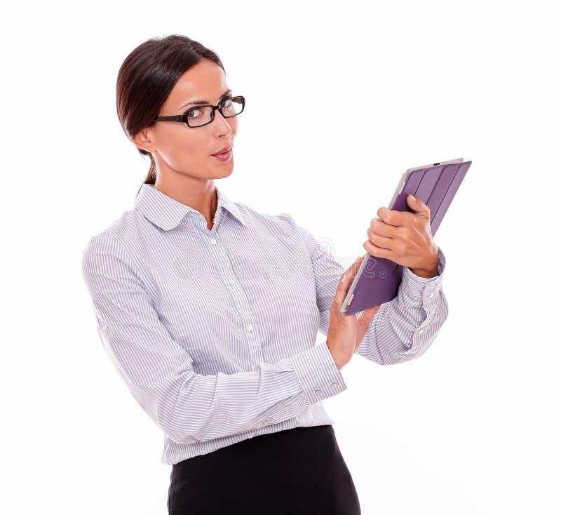 Denkende Brunettegeschäftsfrau mit einer Tablette lizenzfreie stockbilder