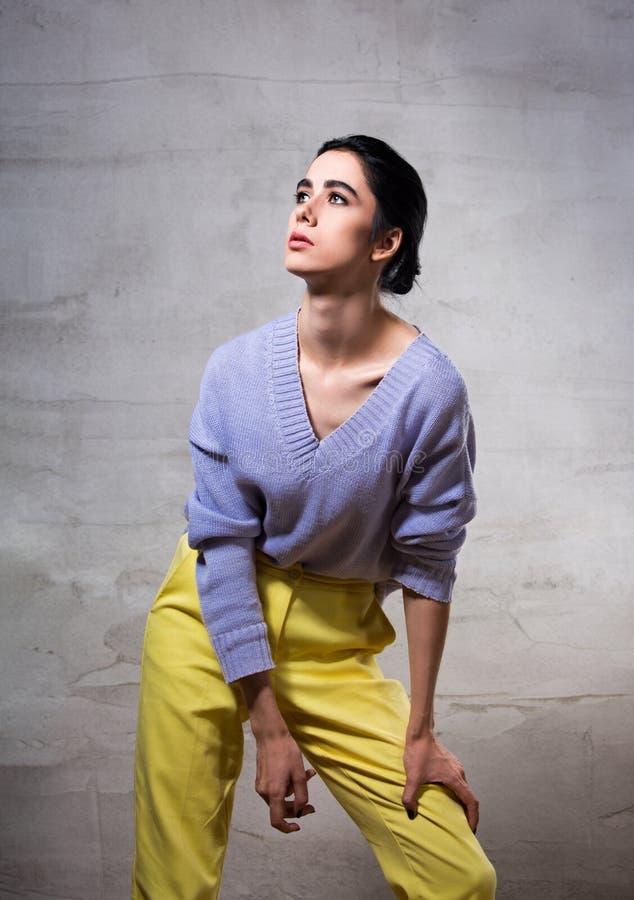 Denkende Frau der schönen Mode, die oben in der violetten Strickjacke und in den gelben Hosen auf grauem Studiohintergrund aufwir lizenzfreie stockfotografie