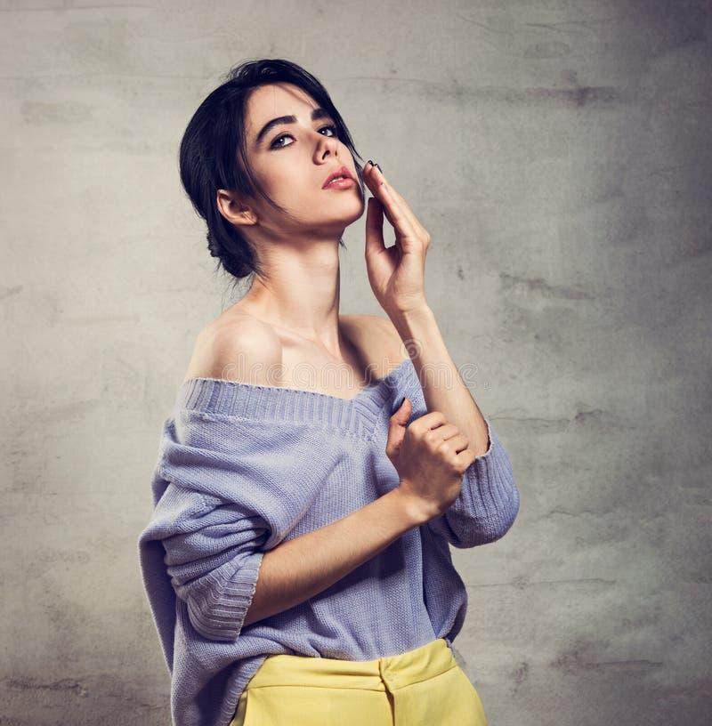 Denkende Frau der schönen Mode, die oben in der violetten Strickjacke und in den gelben Hosen auf grauem Studiohintergrund aufwir stockbilder