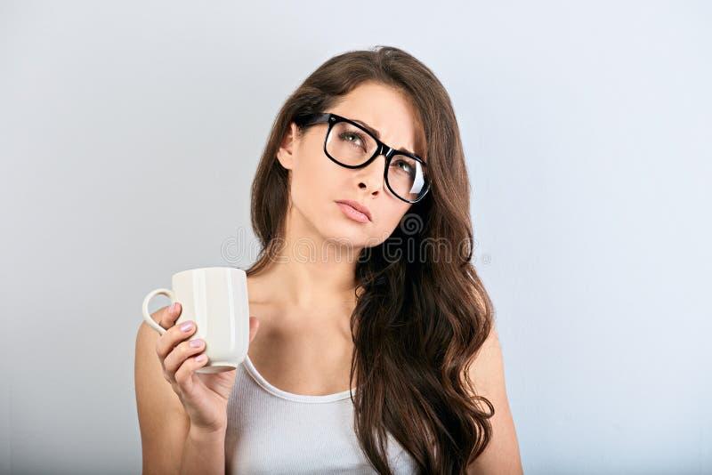 Denkende Frau des schönen Geschäfts in den Brillen, die schauen, hochhalten den Tasse Kaffee Gesicht der Frau stockbild