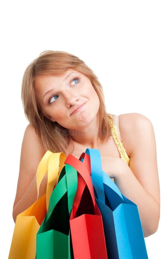 Denkende Frau mit bunten Beuteln stockfoto