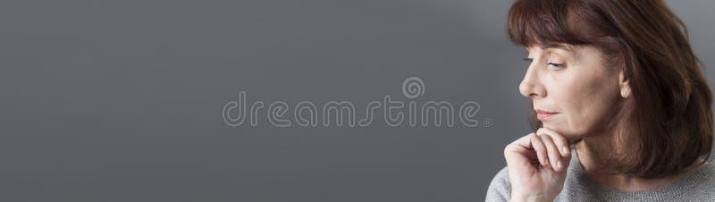 Denkende Frau 50s, die auf Profil, graues langes Panorama meditiert stockfoto