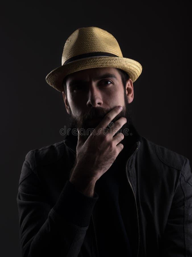 Denkende gebaarde mens die strohoed wat betreft baard dragen die camera bekijken royalty-vrije stock afbeeldingen