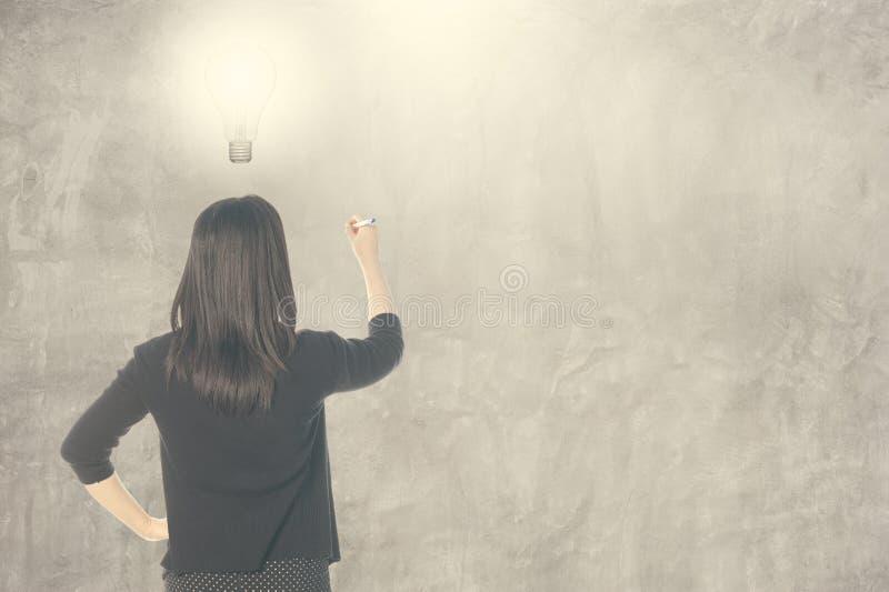 Denkende Ideenbirne der Geschäftsfrau und Schreiben auf leere Wand für Text und Hintergrund lizenzfreie stockbilder