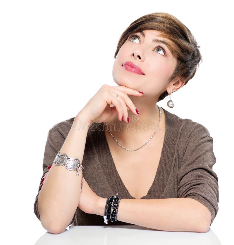 Denkende jonge schoonheidsvrouw die omhoog kijken stock fotografie