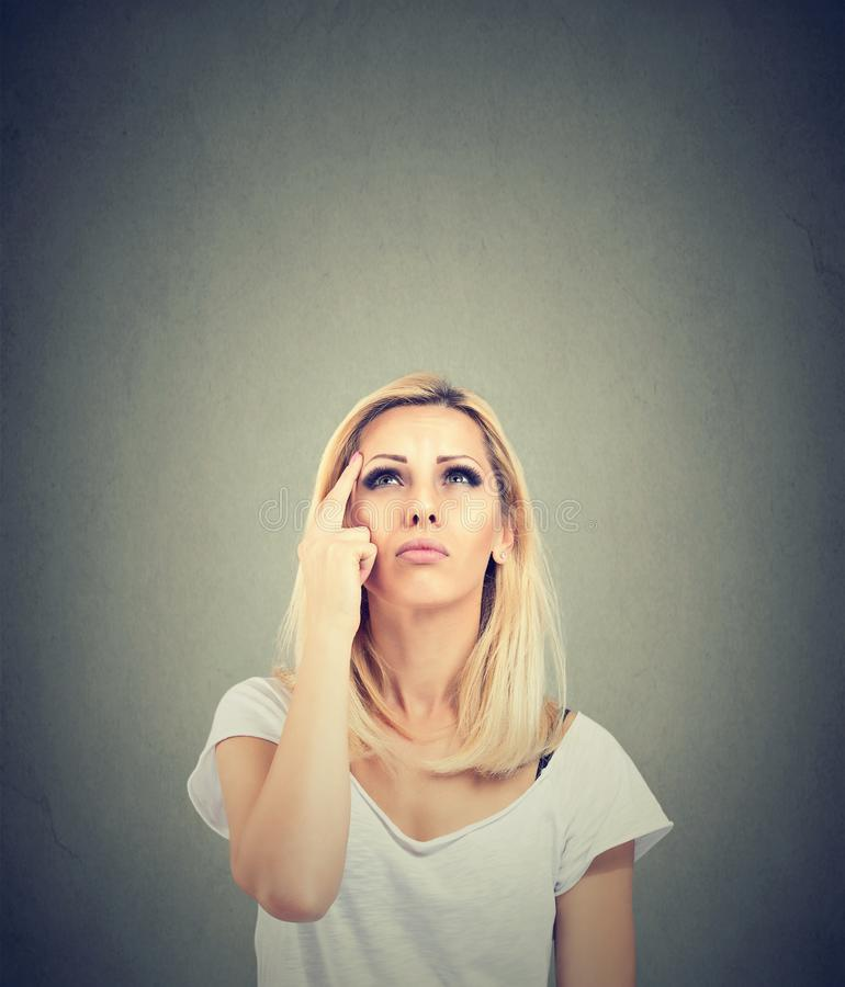 Denkende jonge vrouw die omhoog kijkt stock afbeelding