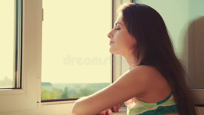 Denkende jonge vrouw die van venster en het genieten van van lucht kijken