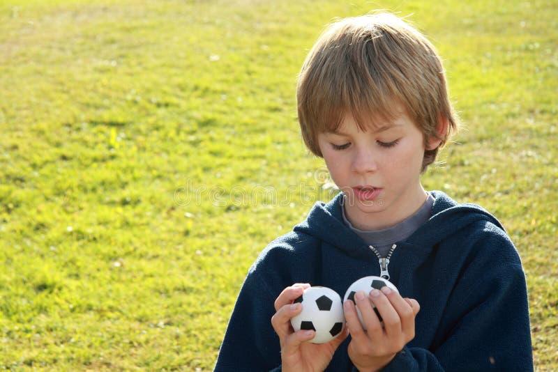 Denkende jongen met twee ballen royalty-vrije stock foto's