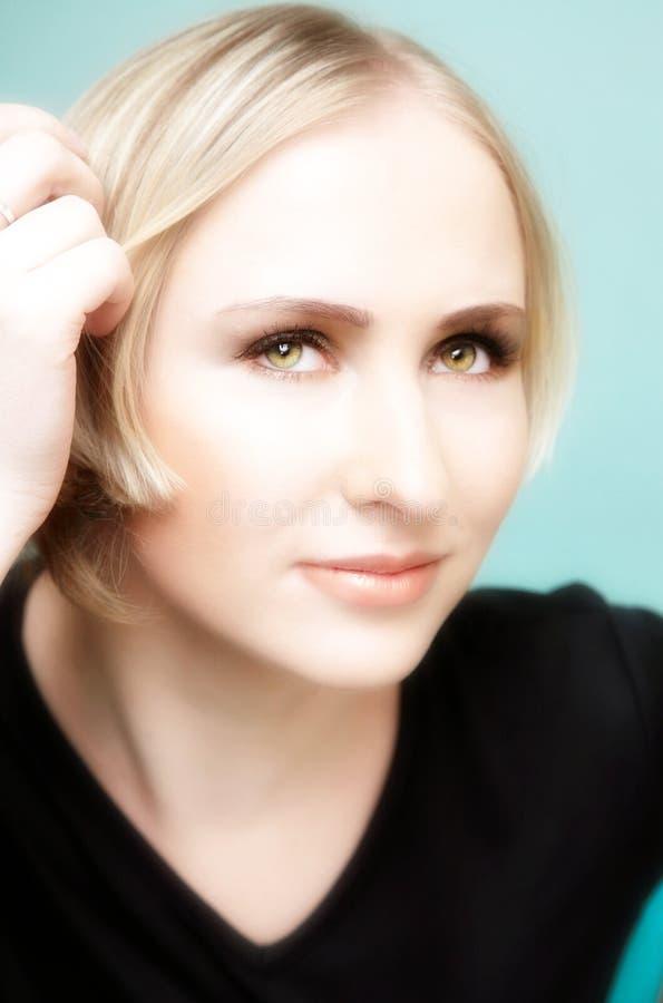 Denkende junge blonde Frau mit grünen Augen lizenzfreie stockfotografie