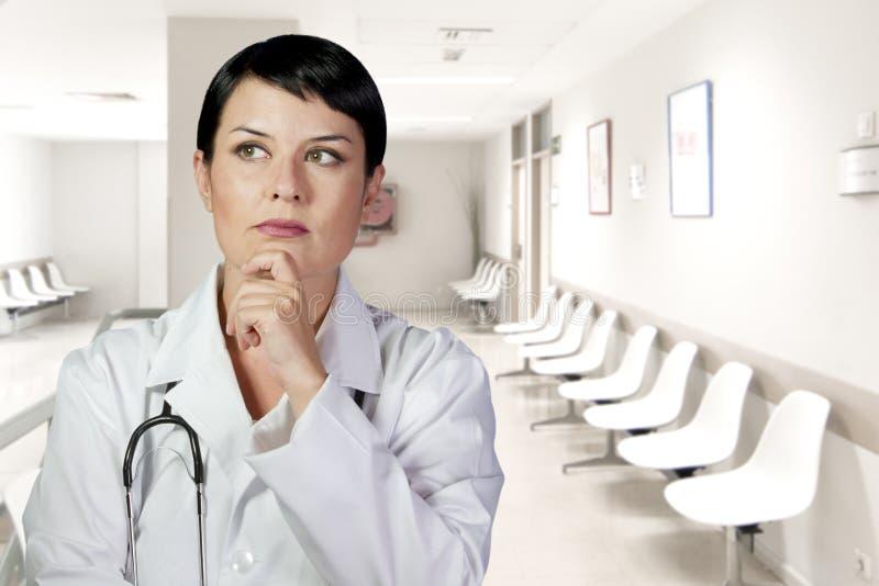 Denkende medische arts die het kijken denken omhoog glimlachend, Medische wom stock foto's