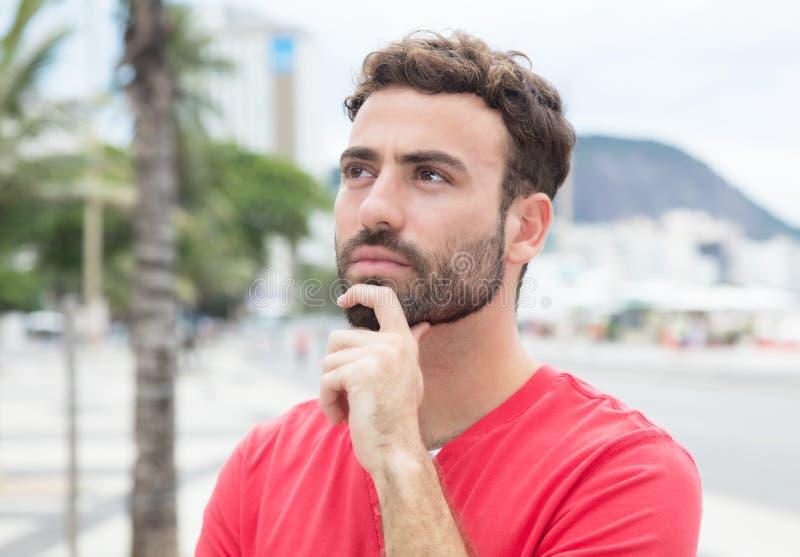 Denkende mens met rood overhemd en baard in de stad stock foto's