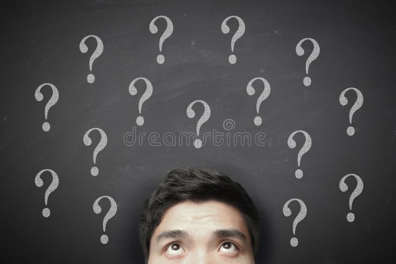 Denkende mens met vraagteken op bord stock foto