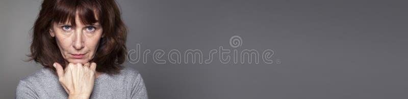 Denkende midden oude vrouw die geloof in zich uitdrukken, grijs panorama stock afbeeldingen