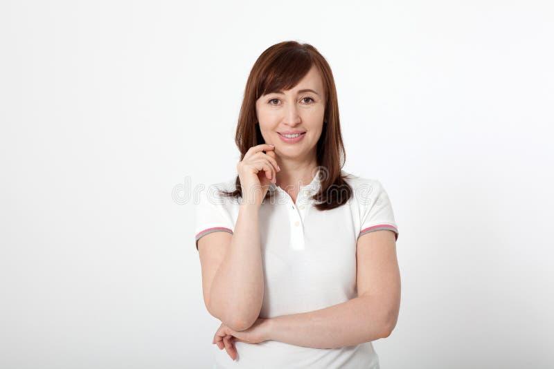 Denkende midden oude vrouw in witte die T-shirt op wit, exemplaarruimte wordt geïsoleerd Moeder en Dochter menopause stock afbeelding