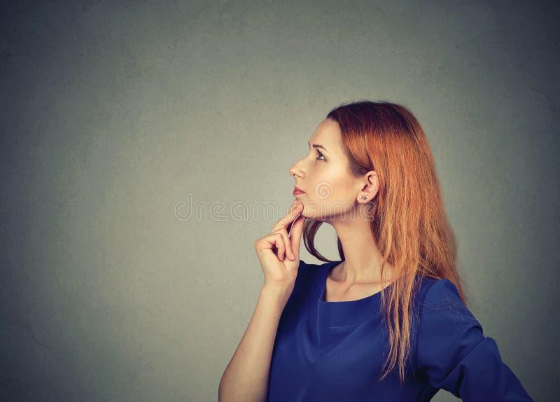 Denkende mooie vrouw op grijs stock afbeeldingen