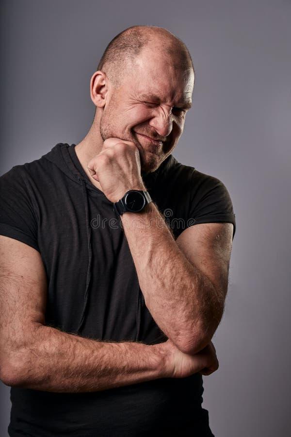 Denkende pret glimlachende mens die één oog en het krassen van het gezicht in zwart toevallig overhemd op grijze achtergrond knip royalty-vrije stock foto's
