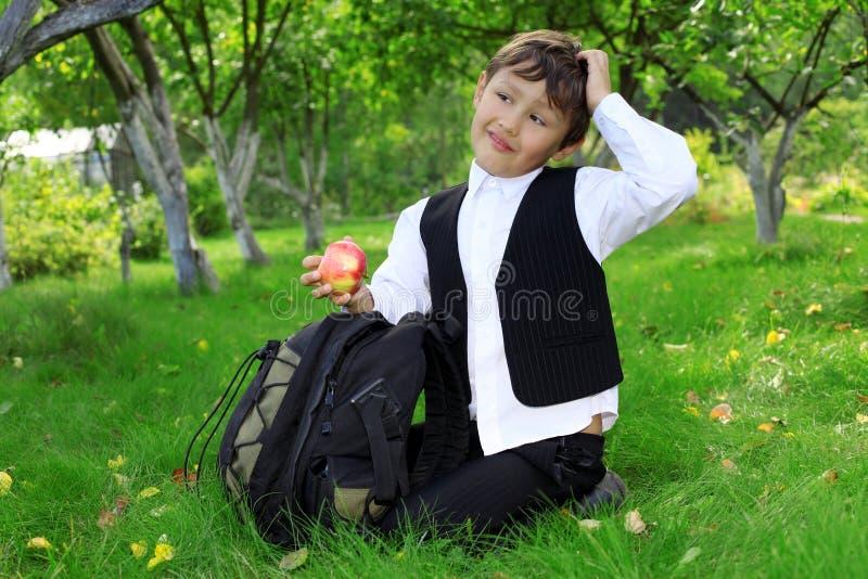 Denkende schooljongen met rugzak en appel stock fotografie