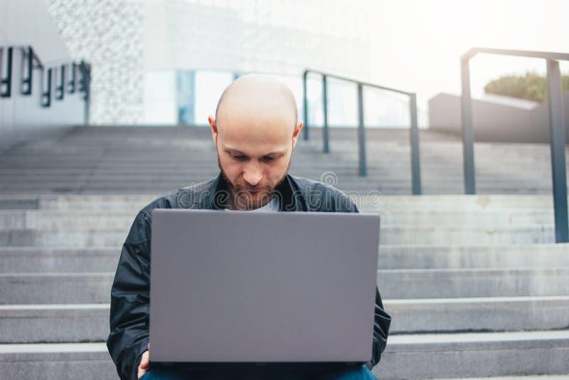 Denkende volwassen succesvolle kale gebaarde mens in zwart jasje die laptop in treden met behulp van bij stad stock afbeeldingen