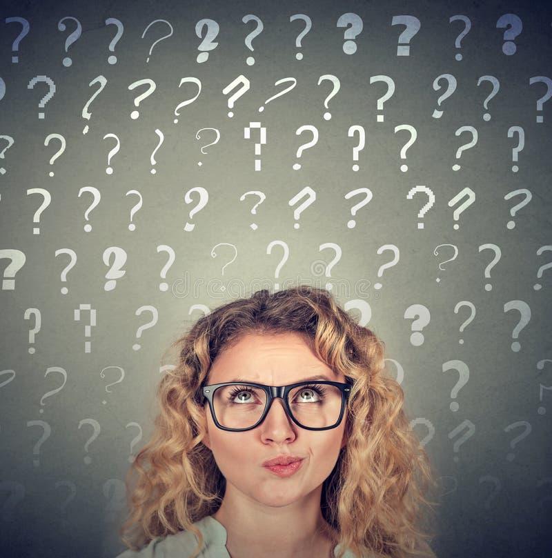Denkende vrouw die omhoog vele vragentekens bekijken boven hoofd stock foto's