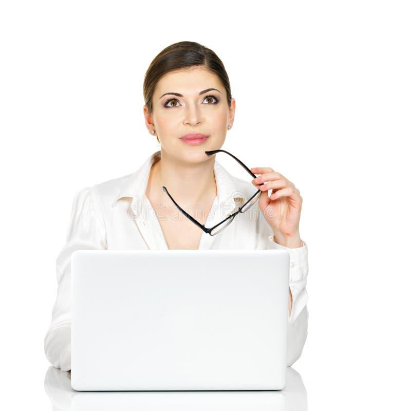 Denkende vrouw met laptop in wit overhemd stock foto's