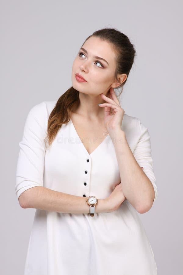 Denkende vrouw in witte kleding die zich op grijze achtergrond bevinden stock foto's