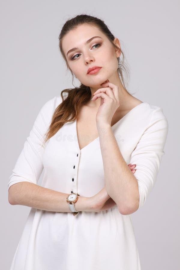 Denkende vrouw in witte kleding die zich op grijze achtergrond bevinden stock fotografie
