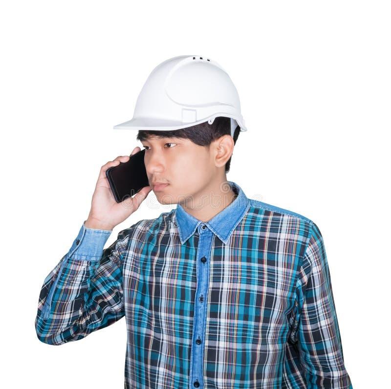 Denkender Befehl des Gesch?ftsmanningenieurs mit Handy und wei?en Schutzhelmplastik auf wei?em Hintergrund tragen stockfotografie