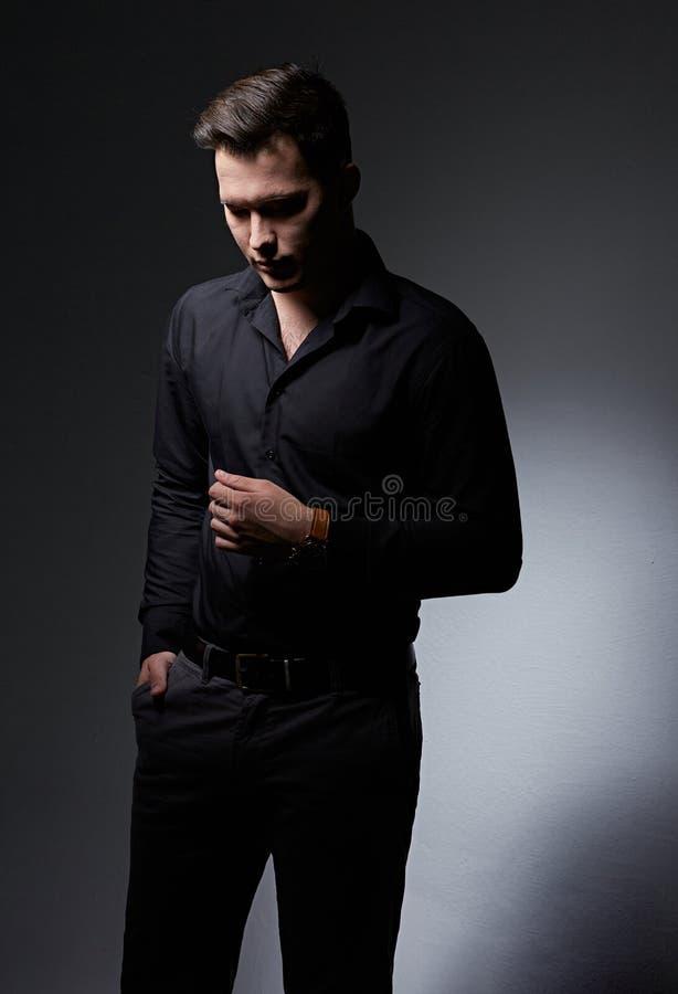 Denkender ernster h?bscher trauriger Gesch?ftsmann, der unten im schwarzen Modehemd und -jeans schauen unten auf Hintergrund des  stockfotografie