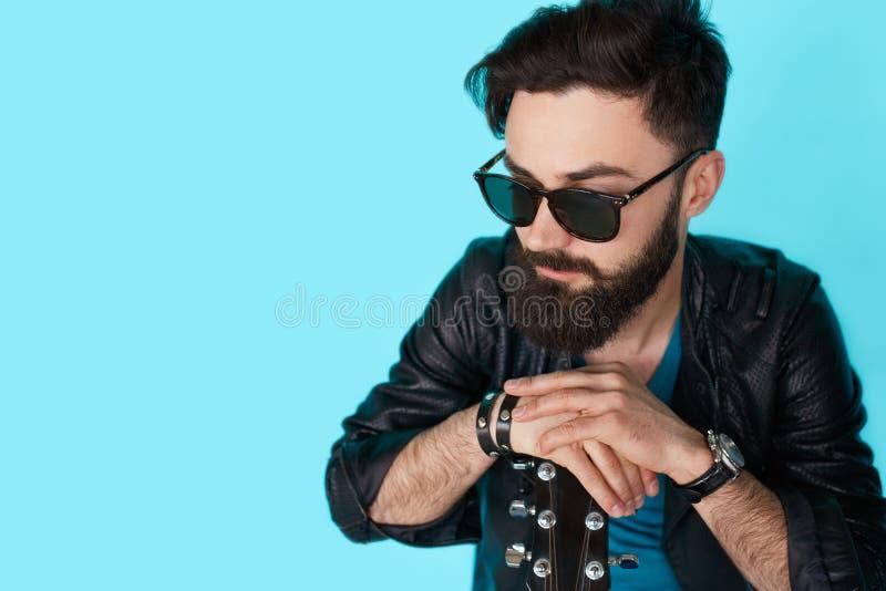 Denkender Felsengitarrist auf blauem Hintergrund stockfotos