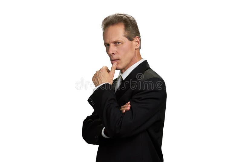 Denkender Geschäftsmann mit dem Finger auf Kinn stockbilder