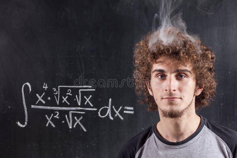 Denkender Junge, der Gleichung mit rauchendem Kopf löst stockfoto