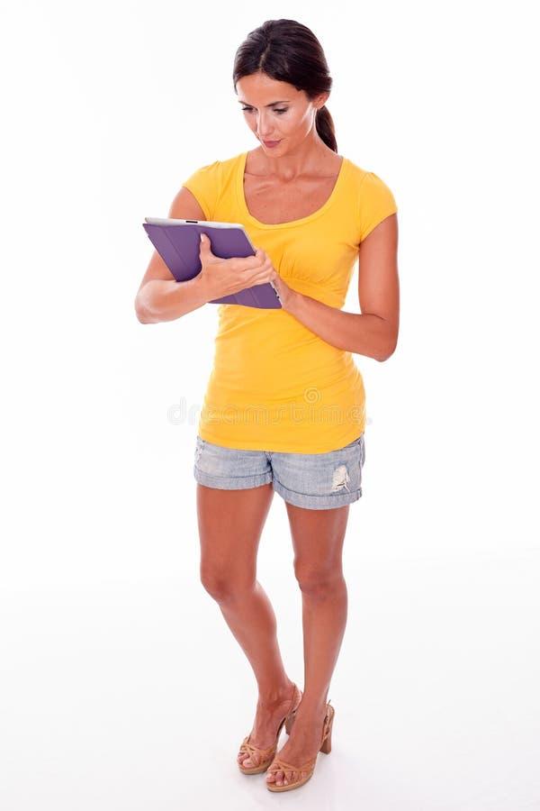 Denkender junger Brunette mit einem Tabletten-PC stockfotografie
