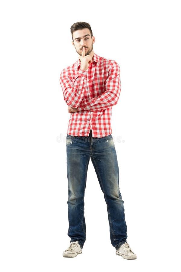 Denkender junger Kerl mit dem Finger über seinem Mund lizenzfreie stockfotos