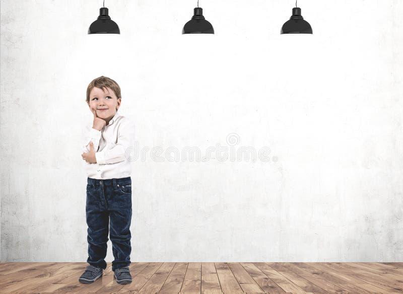 Denkender kleiner Junge im konkreten Raum lizenzfreies stockfoto