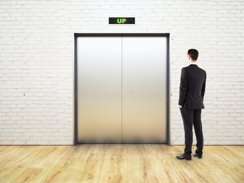 Denkender Mann, der Aufzug betrachtet lizenzfreies stockbild