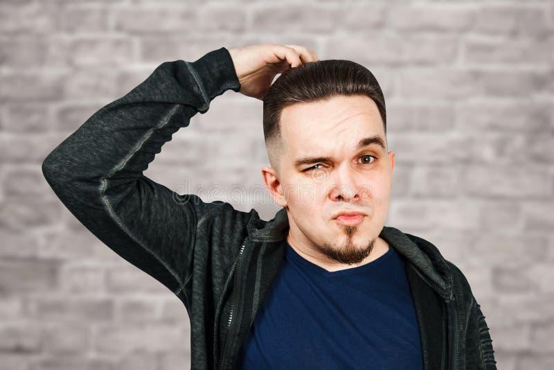 Denkender Mann h?lt Hand am Gesicht, auf Backsteinmauerhintergrund Nahaufnahmeportr?t des jungen nachdenklichen Kerls Kaukasische stockfotos