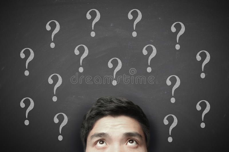Denkender Mann mit Fragezeichen auf Tafel stockfoto