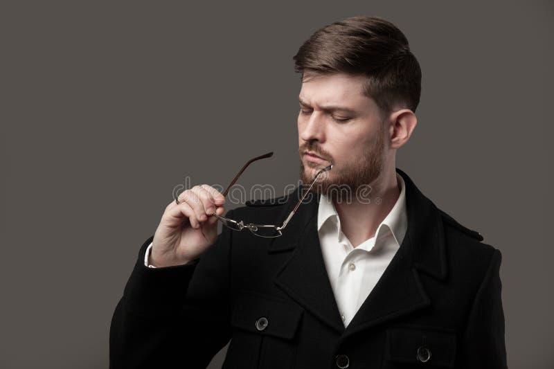 Denkender stilvoller Mann mit dem Bart, der Gläser betrachtet lizenzfreie stockbilder
