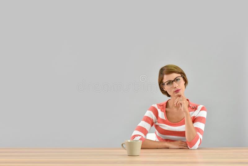 Denkender und trinkender Tee der jungen Frau stockbild
