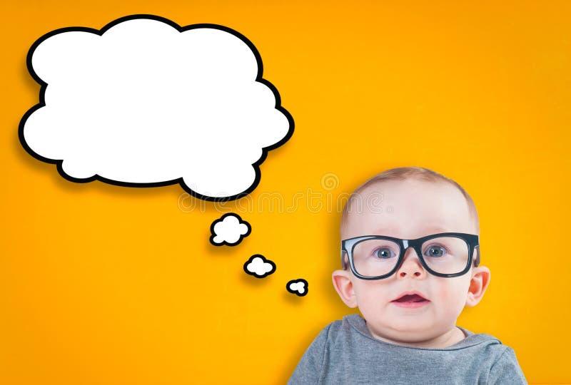 Denkendes Baby mit Gläsern stockfoto