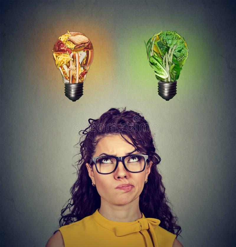 Denkendes Glühlampe der ungesunden Fertigkost und des grünen Gemüses oben betrachten der Frau stockbild