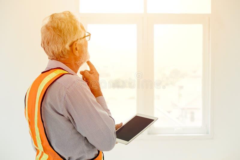 Denkendes Projekt des leitenden Ingenieurs, das Fenster betrachtet lizenzfreie stockfotos