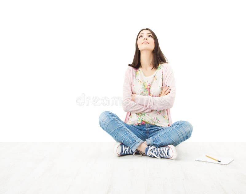 Denkendes Sitzen des schönen Mädchenjugendlichen auf Boden. Weißes backgro lizenzfreie stockbilder