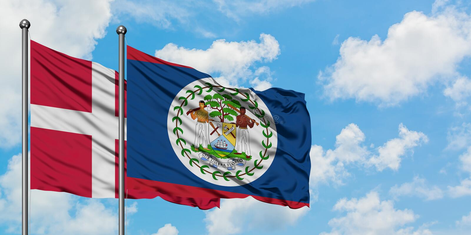Denmark and Belize flag waving in the wind against white cloudy blue sky together. Diplomacy concept, international relations. Consul, diplomat, ambassador royalty free stock image
