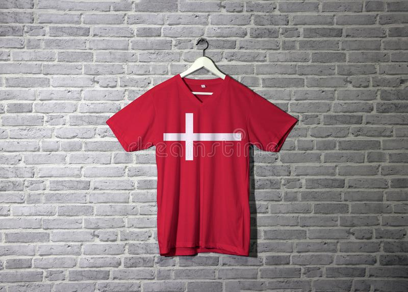 Denmark flag on red shirt and hanging on the wall with brick pattern wallpaper. A white Scandinavian cross on the red stock image