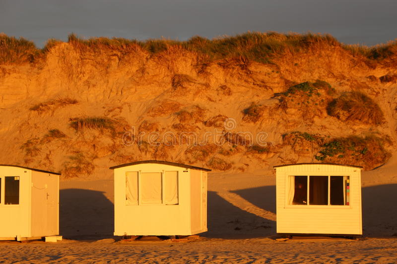 In Denmark, Scandinavia, Europe. Bath houses on the beach of Lokken, Northern Jutland, in evening light royalty free stock images
