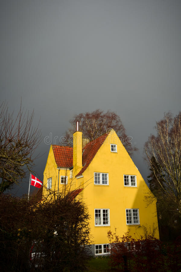 Denmark under gloomy skies. A classic Danish house with yellow-plastered walls and red roof tiles stands is lit up by the sun with gloomy dark-gray skies behind royalty free stock photography