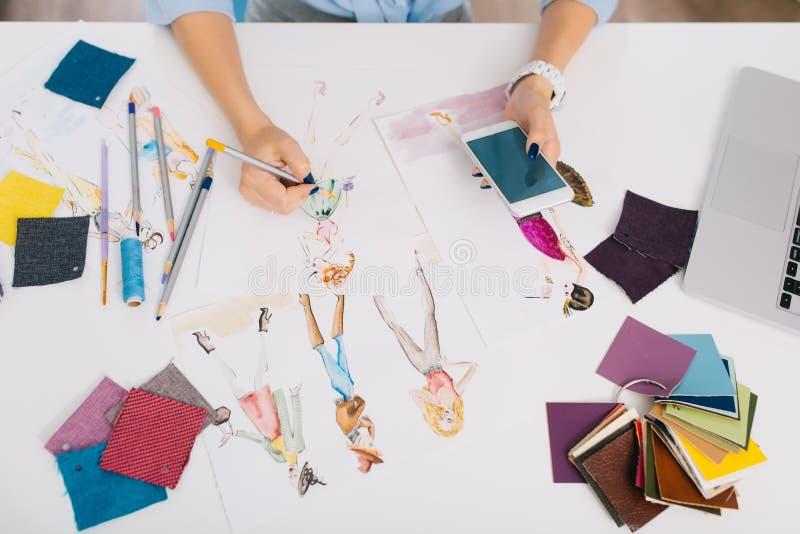 Denna bild beskriver processarna av att planlägga kläder Det finns händer av en flicka som att dra skissar med hjälp av a royaltyfri foto