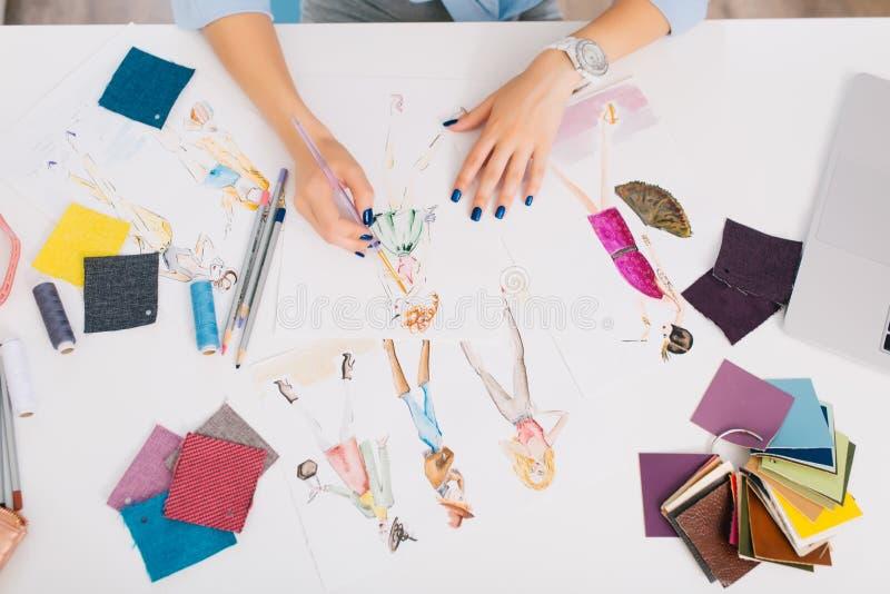 Denna bild beskriver processarna av att planlägga kläder Det finns händer av en flicka som att dra skissar på tabellen fotografering för bildbyråer